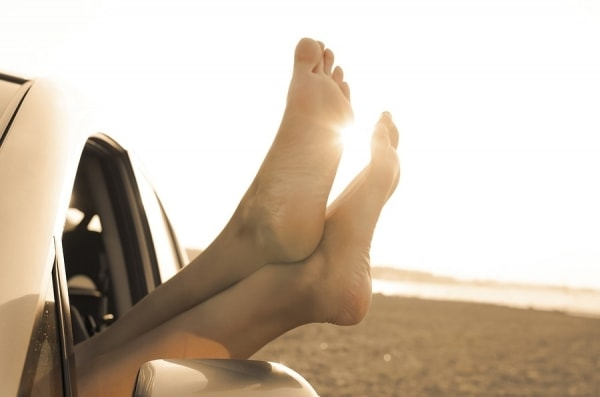 Travel vacation freedom beach vintage concept. Female legs out of car window.